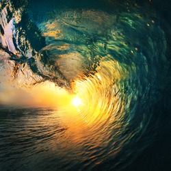 Colored ocean wave breaking at sunset.