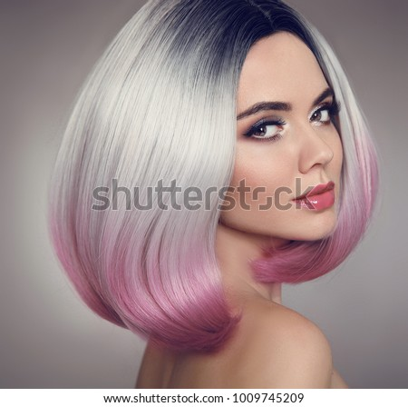 Colored Ombre bob hair extensions. Beauty makeup. Attractive Model Girl blonde with short pink hairstyle isolated on gray background. Closeup woman portrait.