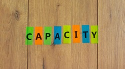 Colored papers with word 'capacity' on beautiful wooden background, copy space. Business concept.
