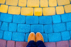 Colored paving tiles with shoes. Paving slabs by mosaic close-up. Walkway in the park under rain. Road paving, construction. Top view.