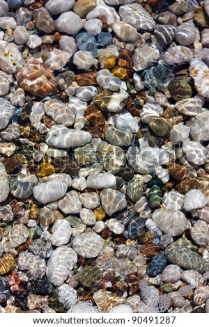 Colored pebbles under water at the coast of Mediterranean sea. Close-up - stock photo