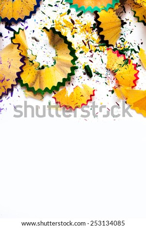 colored pencil shavings on white background with copy space