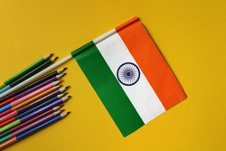 Colored pencils and indian flag on a yellow background.