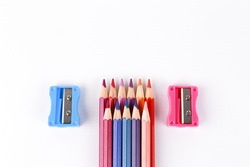colored pencils and pencil sharpeners isolated on white background