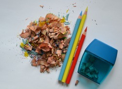 Colored pencils and shavings on white background. Pencil sharpener and crayons, white background
