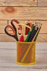 Colored pencils in basket. School or office supplies on wooden background.