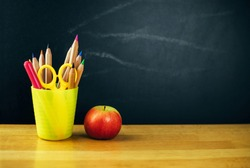 Colored pencils in yellow cup and fresh apple on the table on chalkboard background.