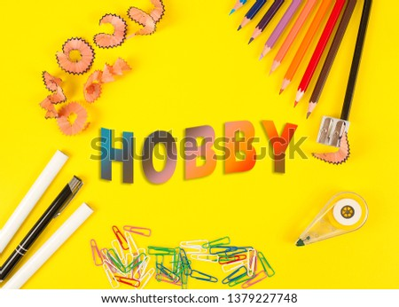 Colored pencils of different colors and a pencil sharpener and pencil shavings on the yellow background. Word Hobby