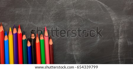 Colored pencils on a black chalkboard - space for caption #654339799