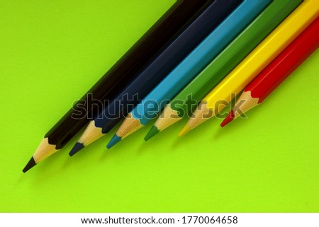 Colored pencils on a green background. Lots of different colored pencils. Colorful pencil. Close. Pencils are sharp. Pencils lie diagonally in the upper right corner. Copy space. Background. Fiat lay.