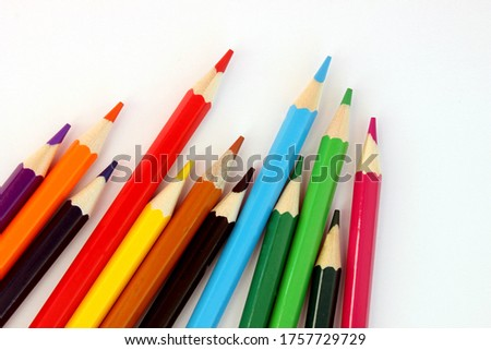 Colored pencils on a white background. Lots of different colored pencils. Colorful pencil. Pencils are sharp. Pencils lie diagonally in the lower left corner. Close-up. Copy space. Background.