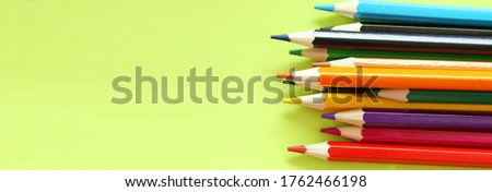 Colored pencils on a yellow background. Lots of different colored pencils. Colored pencil. Pencils are sharp. Pencils are on the right. Close-up. Copy space. Background. Banner