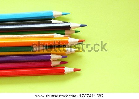 Colored pencils on a yellow background. Lots of different colored pencils. Colored pencil. Pencils are sharp. Pencils are on the left. Close-up. Copy space. Background. Flat lay.