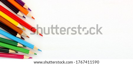 Colored pencils on white background. Lots of different colored pencils. Colored pencil. Pencils sharp. Pencils lie on left. Beautiful background. Close-up. Copy space. Background. Flat lay. Banner.