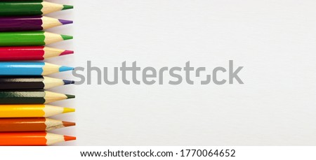 Colored pencils on white background. Lots of different colored pencils. Colored pencil. Pencils sharp. Pencils lie on the left. Beautiful background. Close-up. Copy space. Background. Flat lay. Banner