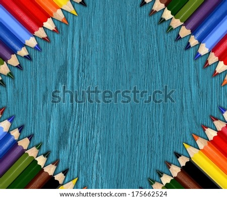 Colored pencils on wooden background, crayons frame - Shutterstock ID 175662524