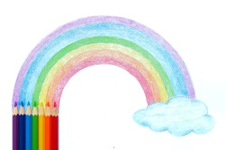 Colored pencils with hand drawing of rainbow and cloud