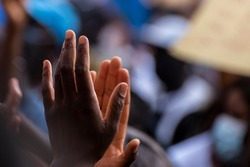 Colored person hands clapping in the middle of a protest against racism, unfocused background