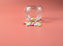 Colored pills scattered from a glass jar, against a bright pink background. Concept of medicine and treatment for coronavirus. Copy space. Selective focus.