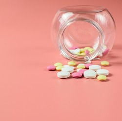 Colored pills scattered from a glass jar, against a bright pink background. The concept of medicine and treatment for coronavirus. Copy space. Selective focus.