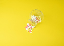 Colored pills scattered from a glass jar, against a bright yellow background. The concept of medicine and treatment for coronavirus. Side and top view. Copy space. Selective focus.
