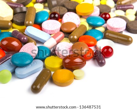 Colored pills, tablets and capsules on a white background - stock photo