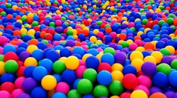 Colored plastic balls in pool of game room. Swimming pool for fun and jumping in colored plastic balls