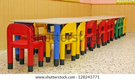colored plastic chairs and a table in the refectory of the preschool children #128243771
