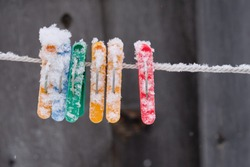 Colored plastic clothes pegs on the clothesline, snow covered