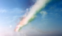 Colored red, white and green clouds, track of airplane on blue sky background, horizontal view. Colors of italian flag.