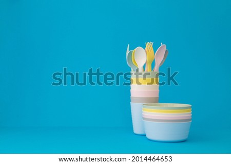 Colored reusable plates glasses spoons and forks on blue background copy space. Tableware for serving in pastel colors for a children's party Photo stock ©