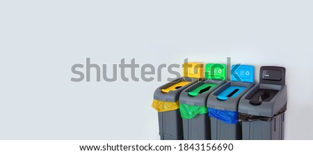 Colored Rubbish Containers for Separate Sorting of Garbage. Bins for Recycling Different Types of Waste Plastic, Glass, Paper, Trash near the White Wall. Sorting garbage Bin or Bags of Different Color Foto stock ©