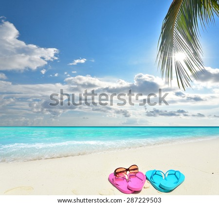 85ba2ec33 Colored sandals and sunglasses at the tropical beach -- Tropical beach  vacation and travel concept