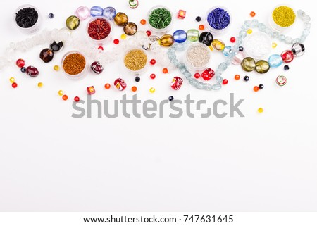 Colored shaped beads, glass beads seed and bugle beads in tubes for christmas decoration on white background. Space for text.