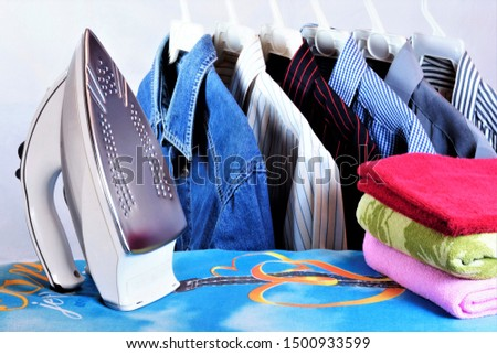 Colored shirts on a hanger, electric iron, towels, Ironing Board in the Laundry room. Ironing clothes with a heated iron, the fabric acquires a smooth surface. Ironing is done after washing.