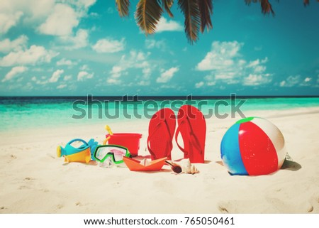 Colored slippers, toys and diving mask at beach - Shutterstock ID 765050461