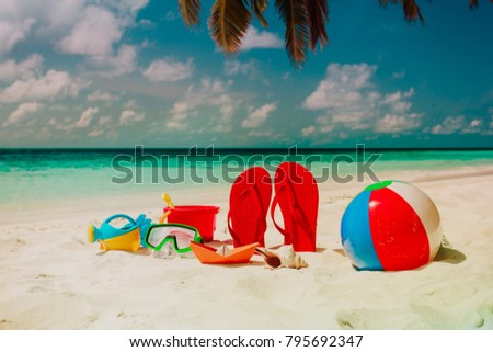 Colored slippers, toys and diving mask at beach #795692347