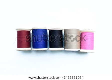 Colored spools of cotton thread isolated on white #1433539034