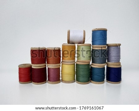 Colored spools of sewing thread on a white background. Sewing masks, clothes, multi-colored rainbow-colored threads. Small spools of colored thread stand in several rows, a wall of spools of thread on