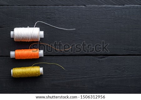 Colored spools of thread for sewing on a wooden black background. Copy space  #1506312956