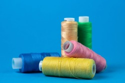 Colored spools of thread on a blue background. Sewing and needlework concept.