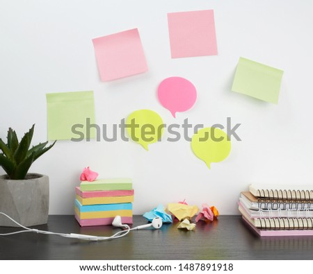 colored stickers attached to a white wall, on the table a stack of notepads, headphones and a flower in a pot,  workplace