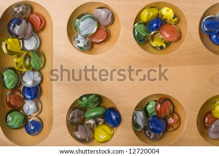 Colored stones of Mancala game in their holes on board