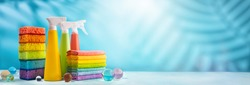 Colored supplies for cleaning on blue background.Spray Bottles of detergent, sponges and rags rainbow colors. Concept of spring cleaning home.