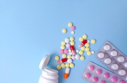 Colored tablets in bulk and in blisters on a blue background flat lay. Medicine, pharmaceuticals concept. Stock photography with copy space, selective focus.