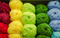 Colored threads for knitting in skeins are on  shelf. Materials for needlework. Knitting on knitting needles.