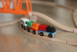 Colored toy cars on wooden rails. Early development of children. Educational toys constructor and steam engine for kids