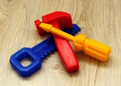 Colored toy plastic tools hammer, saw and screwdriver, lying on a wooden surface