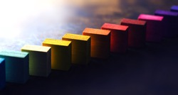 Colored wooden blocks diagonally aligned on old vintage wooden table. For something with concept of variations or diversity. Plenty of copyspace. Shallow depth of field.