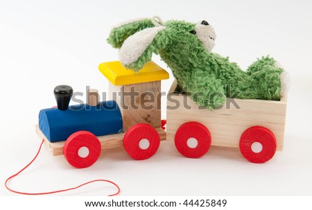 colored wooden toy train with green toy hair on white background